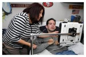 JOAN BARNETT LEE / jlee@modbee.com - Anthony De La Garza 37yrs is pictured at his home in Empire with his mother Josie Halcon on Thursday morning (12-22-11). He had a stroke 10 years ago that paralyzed him from the neck down. He recently got a Tobii comunication device that allows him to use eye movements to manuever it. He is now taking an online history class at MJC. - -